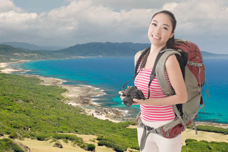 avocation: Happy smiling Asian young female backpacker with camera standing in front of beach of Kenting, Taiwan, Asia.