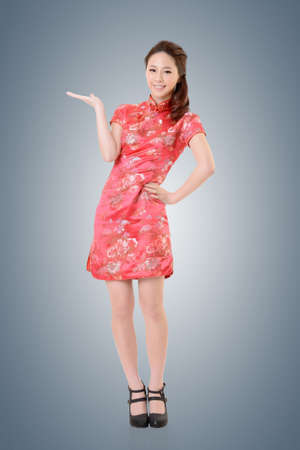 chipao: Smiling Chinese woman dress traditional cheongsam and introduce. Stock Photo