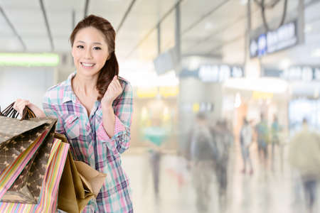 shopper: Exciting young shopping woman hold bags, closeup portrait with copyspace.