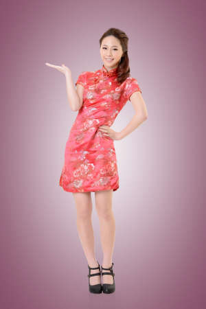 introduce: Smiling Chinese woman dress traditional cheongsam and introduce. Stock Photo