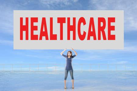 autocuidado: Mujer que sostiene la tarjeta con el texto de la asistencia sanitaria en él contra el cielo.