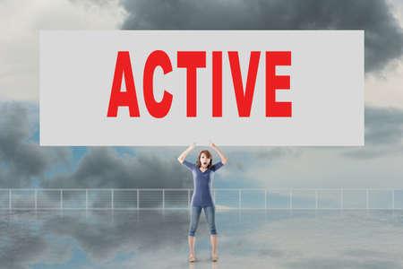 autocuidado: Mujer que sostiene la tarjeta con el texto activo en él contra el cielo. Foto de archivo