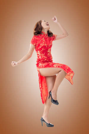 chipao: Smiling and excited Chinese woman dress traditional cheongsam at New Year, studio shot isolated.