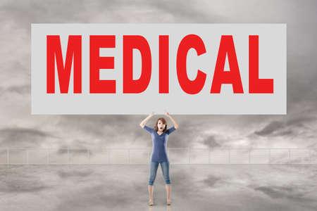 autocuidado: Mujer que sostiene la tarjeta con el texto médico en él contra el cielo.