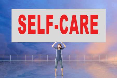 autocuidado: Mujer que sostiene la tarjeta con el texto de autocuidado en él contra el cielo. Foto de archivo