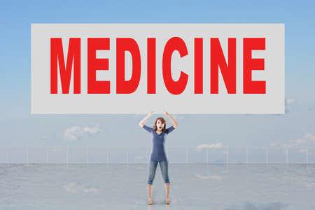 autocuidado: Mujer que sostiene la tarjeta con el texto de la medicina en él contra el cielo.