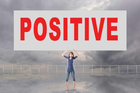 autocuidado: Mujer que sostiene la tarjeta con el texto positivo en él contra el cielo.