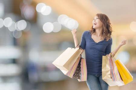 comprando: Compras de la mujer alegre de celebraci�n de las bolsas asi�ticas. Foto de archivo