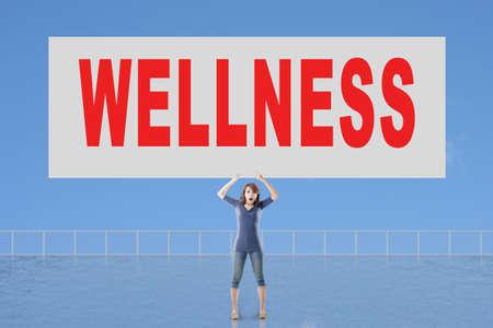 autocuidado: Mujer que sostiene la tarjeta con el texto de bienestar en él contra el cielo. Foto de archivo