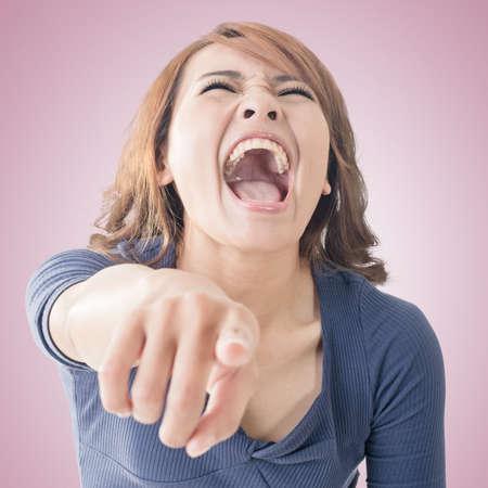 Asijské žena ukazuje a směje se na tebe, detailním portrét. Reklamní fotografie