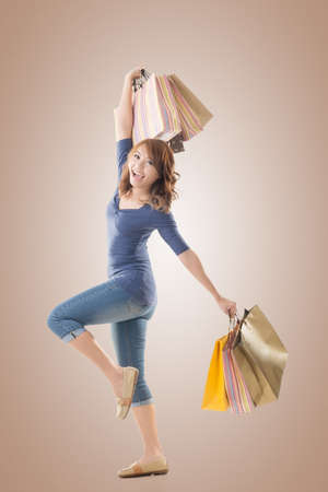 excitation: Cheerful shopping woman of Asian holding bags, isolated. Stock Photo