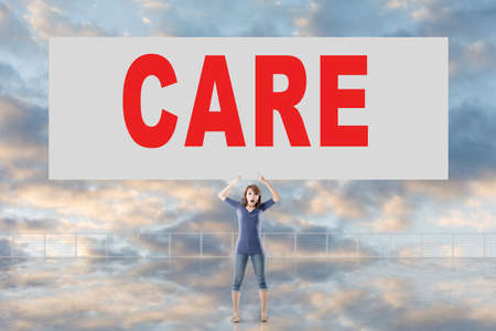 selfcare: Mujer que sostiene la tarjeta con el texto de la atención en él contra el cielo. Foto de archivo