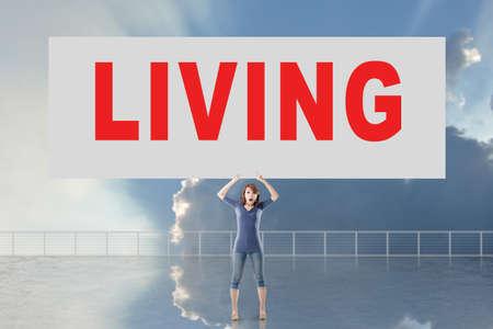 autocuidado: Mujer que sostiene la tarjeta con el texto que viven en él contra el cielo.