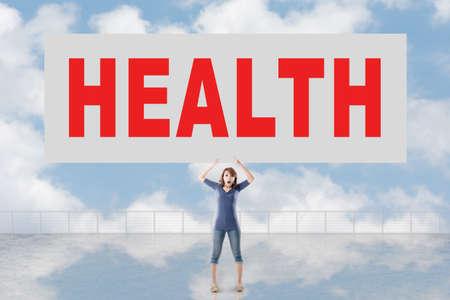 autocuidado: Mujer que sostiene la tarjeta con el texto de la salud en él contra el cielo.