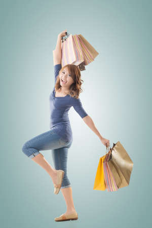 lifestyle shopping: Cheerful shopping woman of Asian holding bags, isolated. Stock Photo