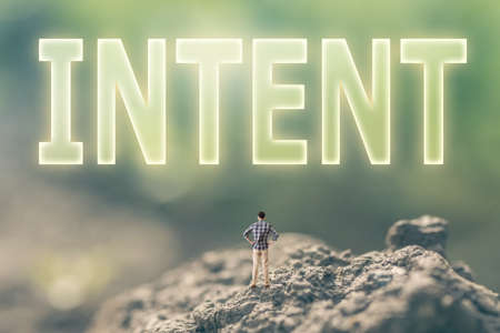 intent: Concept of goal with a person stand in the outdoor and looking up the text over the sky in nature background. Stock Photo