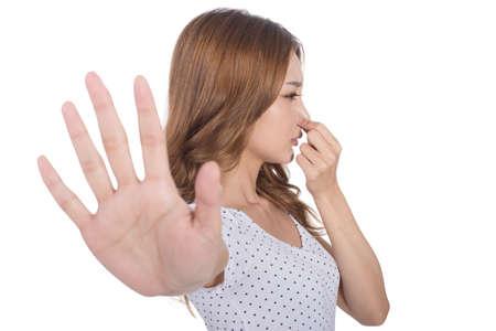 Portret van een jonge vrouw die haar neus als gevolg van een slechte geur.