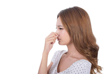 stink: Portrait of a young woman holding her nose because of a bad smell.