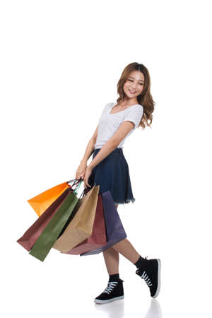 asian lady: Smiling happy Asian woman shopping and holding bags, full length portrait isolated. Stock Photo