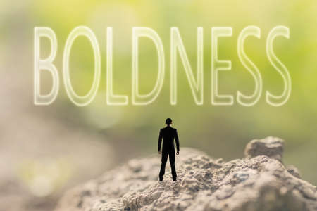 boldness: one person stand in the outdoor and looking up text on nature background, concept of courage Stock Photo