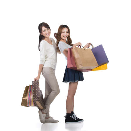 happy shopping: Happy smiling shopping girls of Asian holding bags with her friends. Stock Photo