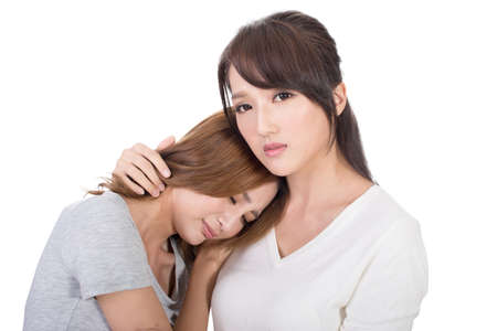 asian group: Troubled young girl comforted by her friend. Stock Photo