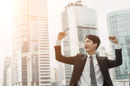 victory: Cheerful Asian business man of success. Stock Photo