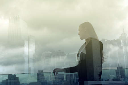Silhouette of businesswoman stand and look far away in Hong Kong, Asia. Double exposure. Imagens