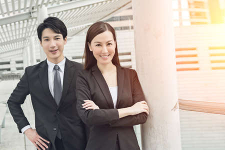 Asian business man and woman in the street, Hong Kong, China.