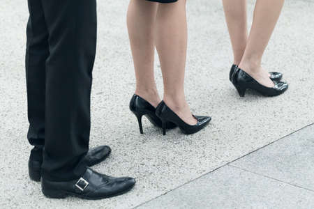 body line: Business woman and man wait in line, closeup image with part of body.