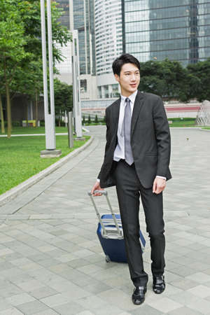 baggage: Asian business man hold a luggage case and walk in the city.
