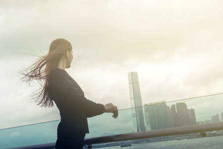 far away: Silhouette of businesswoman stand and look far away in Hong Kong, Asia. Stock Photo
