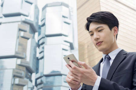 Confident young Asian businessman using cellphone, concept of business, technology, social media etc. Standard-Bild