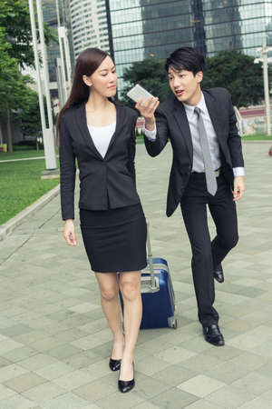 dragging: Young businessman talk a phone to his boss in the city.