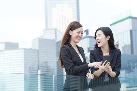 and in asia: Asian business women talking to each other in Hong Kong, Asia.
