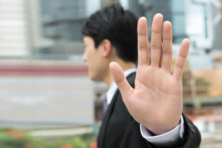 negativity: Stop gesture, side view of Asian businessman standing in the city.