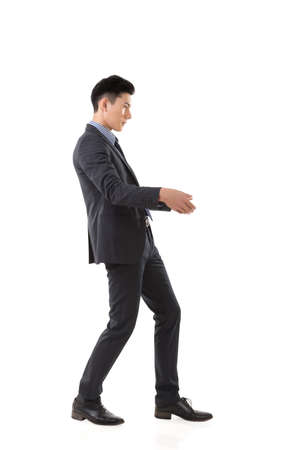 Holding pose of Asian business man, full length isolated. Stock Photo