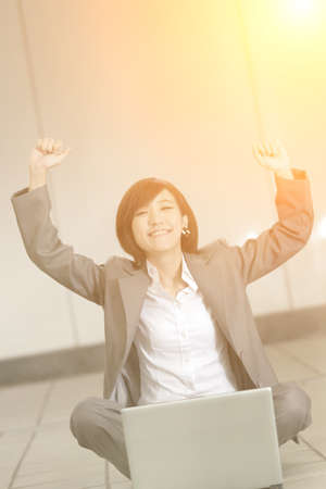 at ease: Cheerful business woman sitting and using laptop on ground. Stock Photo