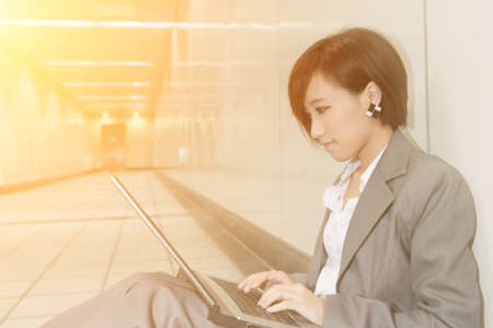 sitting on the ground: Asian young business woman using laptop and sitting on ground inside modern buildings. Stock Photo