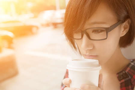 Asian girl holding cup of coffee at street in raining day in Taipei, Taiwan.