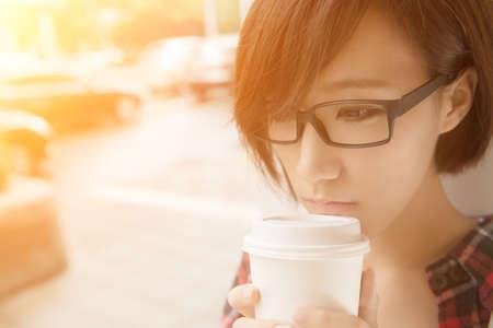 Aziatisch meisje dat kopje koffie op straat in regent dag in Taipei, Taiwan.