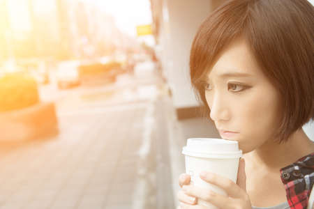 young asian: Asian girl holding cup of coffee and standing and waiting on street in raining day in Taipei, Taiwan.