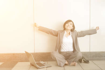 at ease: Asian young business woman take off her shoes and relax sitting on ground in modern building. Stock Photo