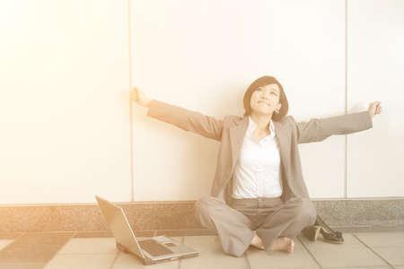 Mujer de negocios joven asiático quitarse los zapatos y relajarse sentado en el suelo en el edificio moderno.