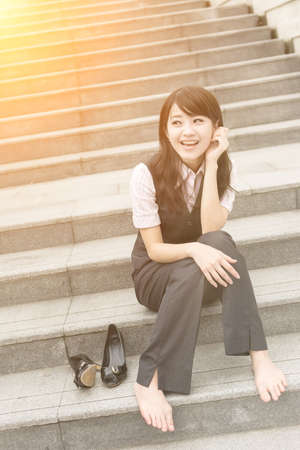 shoes off: Happy smile business woman rest and take off her shoe in outside of urban. Stock Photo