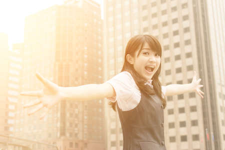 raised hand: Exciting business woman raised hand in outside of city. Stock Photo