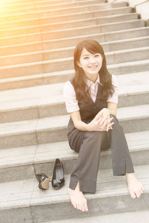 shoes woman: Happy smile business woman rest and take off her shoe in outside of urban. Stock Photo