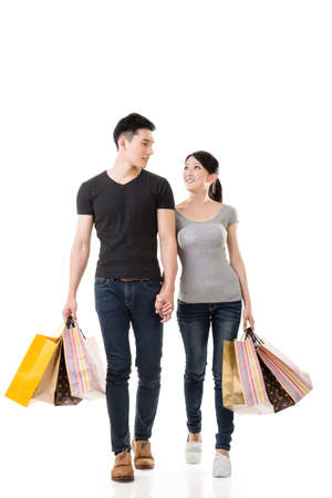 Asian couple shopping, full length portrait isolated