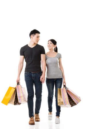 Asian couple shopping, full length portrait isolated