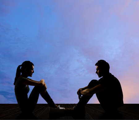 Silhouette of young couple face to face sit on ground in the city night.